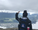 Alexis Romo, a junior psychology major, displays the Wildcat hand symbol high in the Austrian Alps during the Medieval Europe Study Tour.