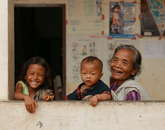 Erin Galligan, a graduate student studying nursing, takes a photo of a great grandmother and her family during the Nurse Anesthesia program in Laos, Cambodia.