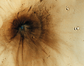 This impact occurred between December 2003 and November 2005. The main crater itself is only 23 meters across, but the impact event created markings spreading more than a kilometer outward. The interior stands out as blue because the impact excavated a cavity into rocks below the surface that has a different composition than the overlying dust. Some distant dark-toned spots and streaks were created when ejecta from the main crater flew out and reimpacted the surface, producing chains of secondary craters.