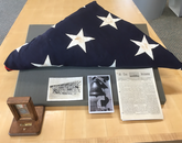 Housed at Special Collections: a 48-star flag that flew over the USS Arizona, represented in a left-shoulder patch on the jersey; Esther Ross' medallion worn at the ship's christening and launch, represented on the front collar; a photo of the 1931 USS Arizona football team, whose jerseys inspired the helmet's Block A style; a photo of the bell, represented in a helmet decal; and a copy of At Em Arizona, the ship's newspaper and also its rallying cry, represented in lettering on the back of the helmet.