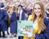 """Kira Baum, who graduated with a marketing degree, shows off her mortar board, which she decorated with characters from the popular show """"Rick and Morty."""" Baum, who was a personality on KAMP student radio, plans to work in the music industry."""
