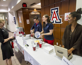 Three volunteers standing at a table making root beer floats.