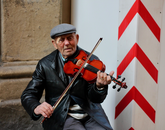 Senior Samara Rosenthal snaps a photo of a man playing violin along a picturesque avenue during the CEA Florence program in Italy.