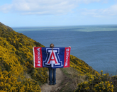 Taylor Fitzgerald, a finance major, strikes a pose with the UA flag along the seaside in the Netherlands.