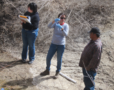 Ruby Sierra of the Environmental Health Sciences Transformative Research Undergraduate Experience program, Paloma Beamer and Arnold Clifford take a core sample in an agricultural field.