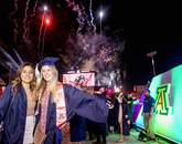 Friends Ciara Valencia, who graduated in political science, and Emily James, a public health graduate, are framed by the fireworks display that traditionally concludes the ceremony. (Photo: John de Dios/UA News)