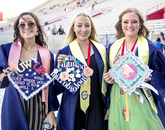 Customized mortarboards are a must for Rachel Radeka, a public health graduate going to nursing school; Sammi Meyer, a microbiology graduate headed to pharmacy school; and Haley Evans, a microbiology graduate planning to become a pathologist's assistant. (Photo: John de Dios/UANews)