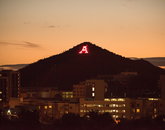 """Proposed by UA football player and civil engineering student Albert H. Condron and built by UA students at a cost of $397, Sentinel Peak's prominent """"A"""" has proclaimed Wildcat spirit across the miles since 1916. Ever since, students from Bobcats Senior Honorary light the letter with flares in preparation for a fresh whitewash, making it one of the University's oldest traditions."""