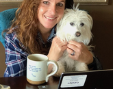 """Carolyn preparing for virtual office hours with help from Cora. Mug with favorite lyric from Prince: 'Dearly beloved, we are gathered here today to get through this thing called life.'"""" – Carolyn Casertano, assistant professor of practice in the Department of Communication"""