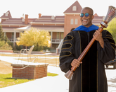Bryan Carter, associate professor of Africana studies and director of the UArizona Center for Digital Humanities, poses with the university's ceremonial mace during filming for the virtual 2020 Commencement. (Photo: Chris Richards/University of Arizona)