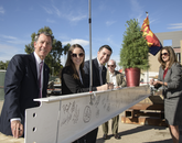 Five attendees stand next to a white steel beam decorated with signatures. From left: Gregg Goldman, UA senior vice president for business affairs and chief financial officer; Aundrea DeGravina and Vianney Careaga, student members of the Arizona Board of Regents; Richard H. Silverman, vice chair of the UA Foundation board of trustees and of counsel at Jennings, Strouss & Salmon PLC; and Lyndel Manson, regent. (Kris Hanning/UAHS BioCommunications)