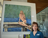 """Harrie Handler, family of Jordan Handler, program coordinator at the University of Arizona BookStores, with her painting, """"I Will Not Be Defined By My Scars. I Am Beautiful."""" The painting won a People's Choice Award. (Photo courtesy of Pamela Wagner)"""