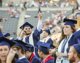 Jesus Gaurdado of Los Angeles, who graduated with a degree in accounting, waves so that his family can find him amid a sea of blue robes in Arizona Stadium. (Photo: John de Dios/UANews)