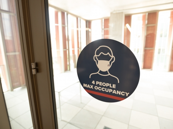 """sign on a window that reads """"4 people max occupancy"""""""