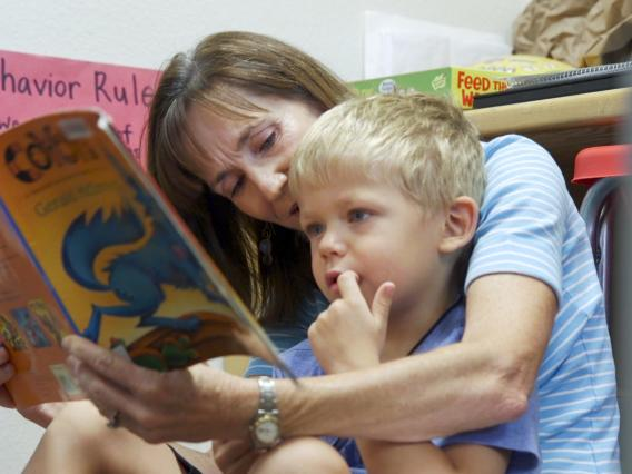 Speech pathologist Rebecca Vance reads to a boy as part of an annual summer camp conducted by the UA's Department of Speech, Language and Hearing Sciences.