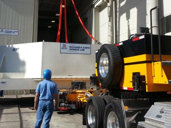 Tucked inside a protective case, the LSST mirror is lowered onto a flatbed trailer to be hauled off to temporary storage.
