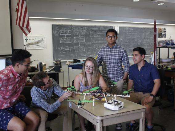 Members of the Terrestrial Exploration project work on their aerial photography vehicle, which blends the vertical takeoff capabilities of a drone with the smooth sailing and endurance of a plane.