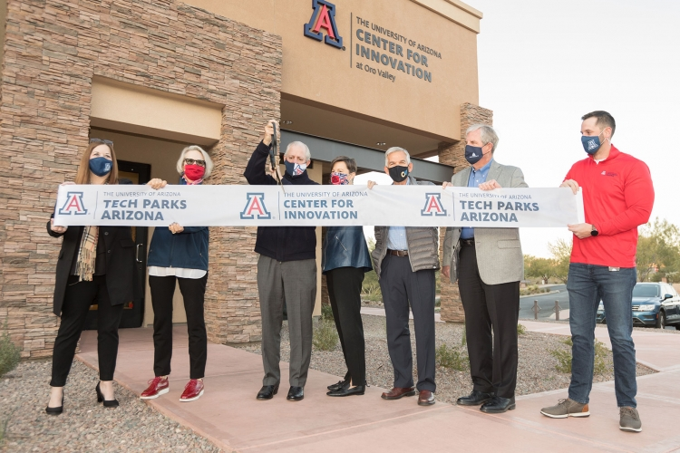 a group of people cutting a ribbon in front of a building