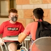 two male students sitting at an outdoor table wearing masks