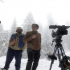 a group of people in a snowy field with filmmaking equipment