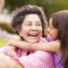 a seated older Hispanic woman smiles as a young girl embraces her shoulders from behind
