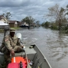 Man on a boat in a flooded neighborhood.