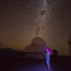 Woman at night in front of telescope