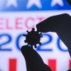 Fingers hold a coronavirus symbol over an election 2020 sign