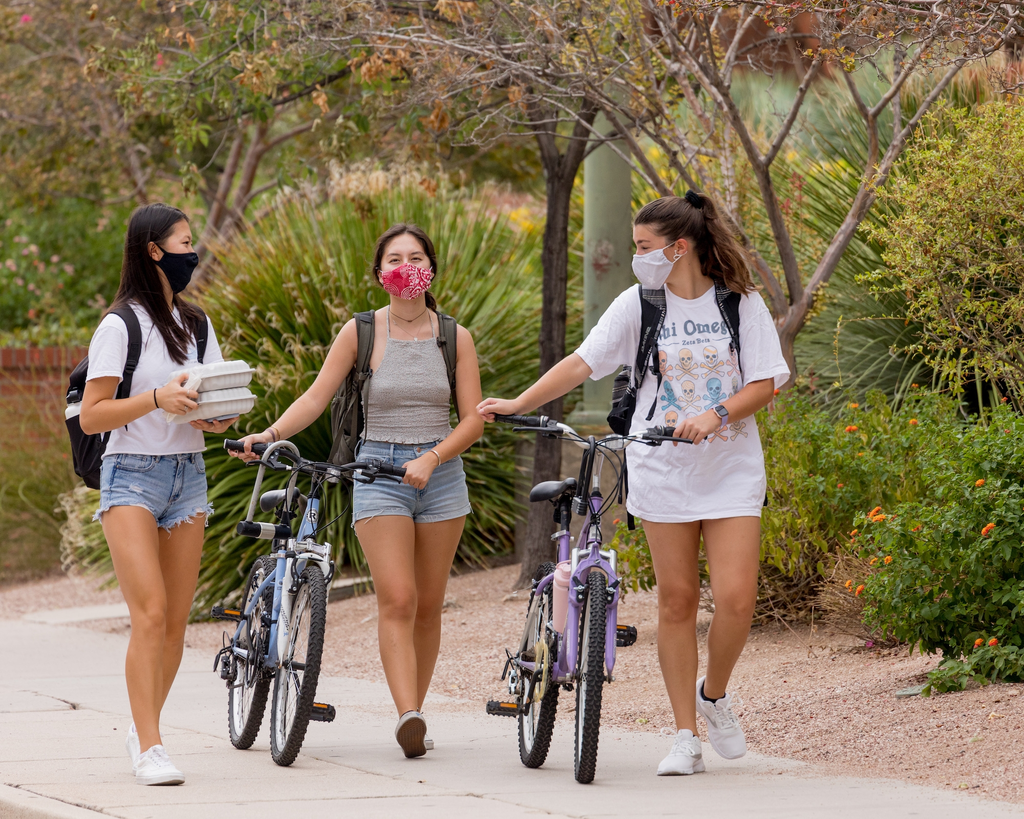 students with face masks walking with bikes on campus
