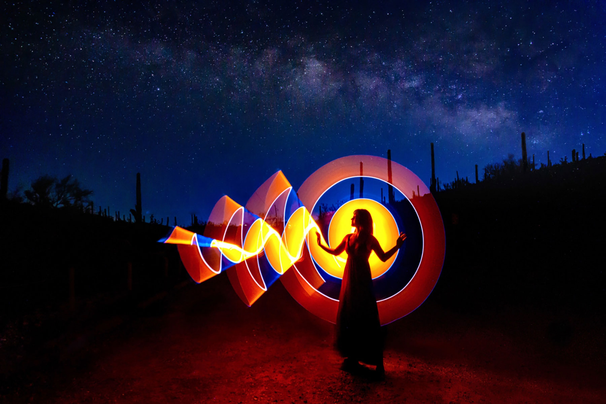 woman standing in a field under a starry sky surrounded by a circle of light