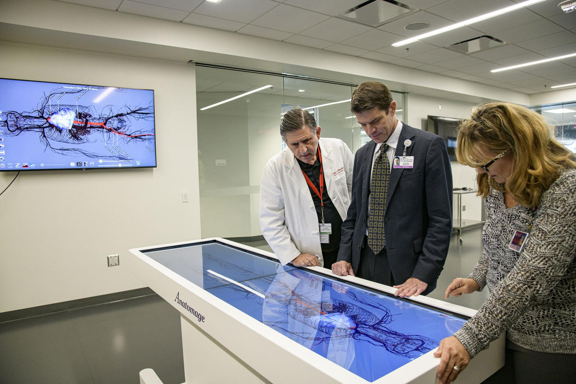 Allan Hamilton, executive director of the Arizona Simulation Technology and Education Center, Kevin Moynahan, College of Medicine–Tucson deputy dean for education, and Deana Ann Smith, health care simulation educator, work on a life-size virtual dissecti