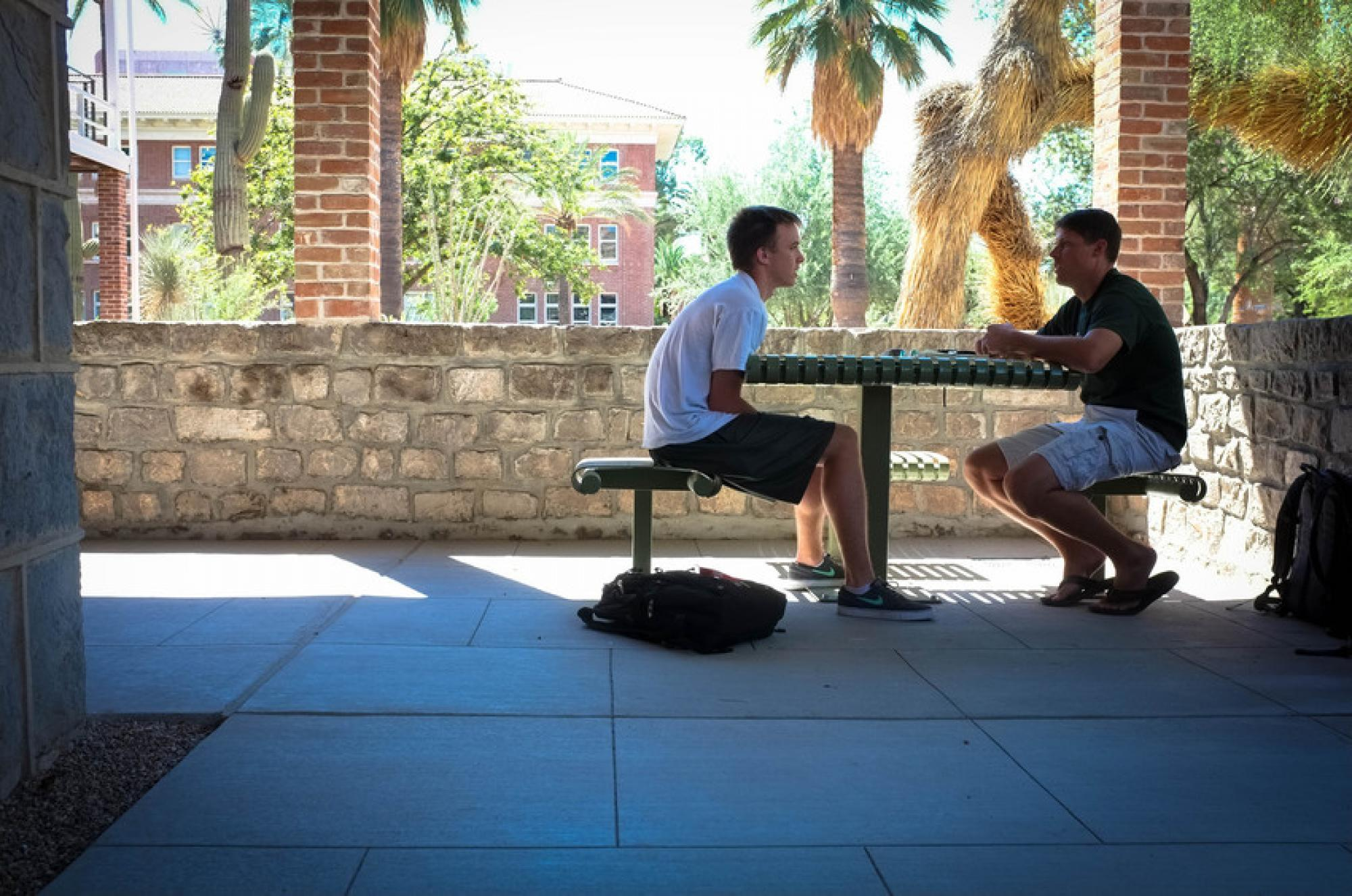 """Sept. 11, 11:30 a.m.: UA alumnus Rich Redel joins Paul Lindvall, a freshman studying engineering, in the shade on the ground floor of Old Main. """"It's a good place for meeting friends to talk with,"""" Lindvall says."""