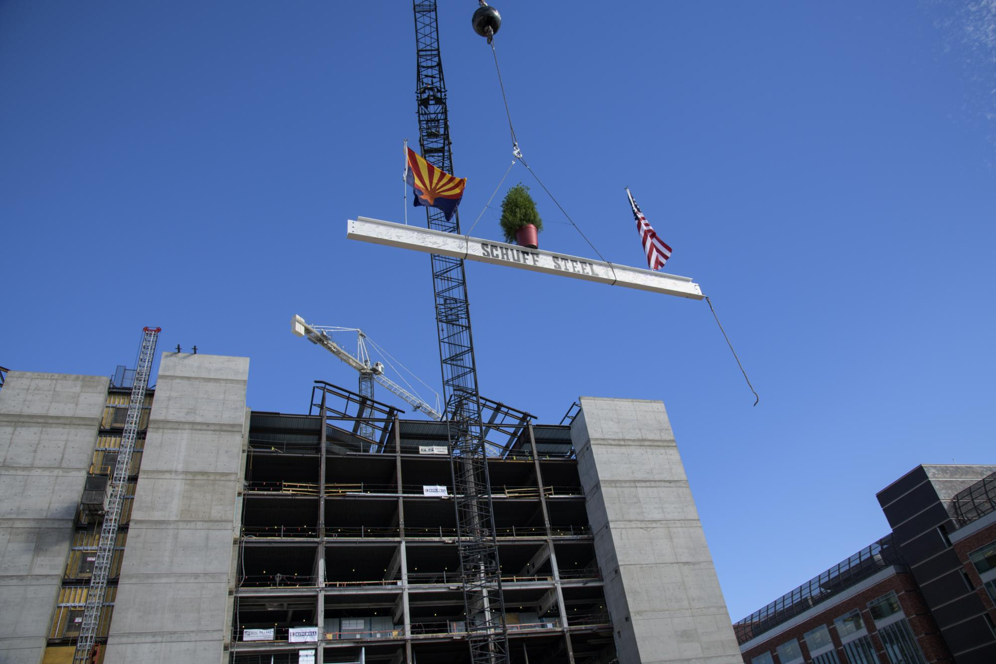 The final steel beam is lifted into place.