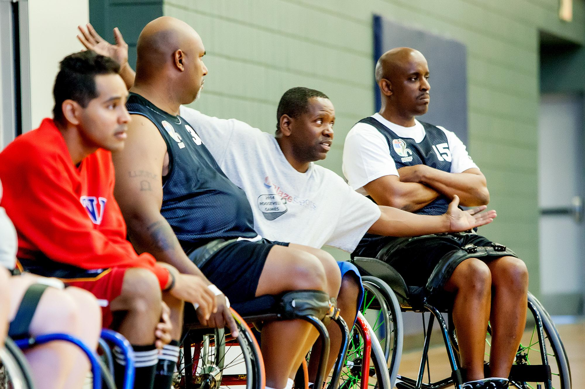 Carl Morgan, from Atlanta, shows his mobility to the coaches during a discussion about positions on a wheelchair basketball team. Morgan is flanked by his friend Derrick McMillon and Robert Jones, both from Georgia.
