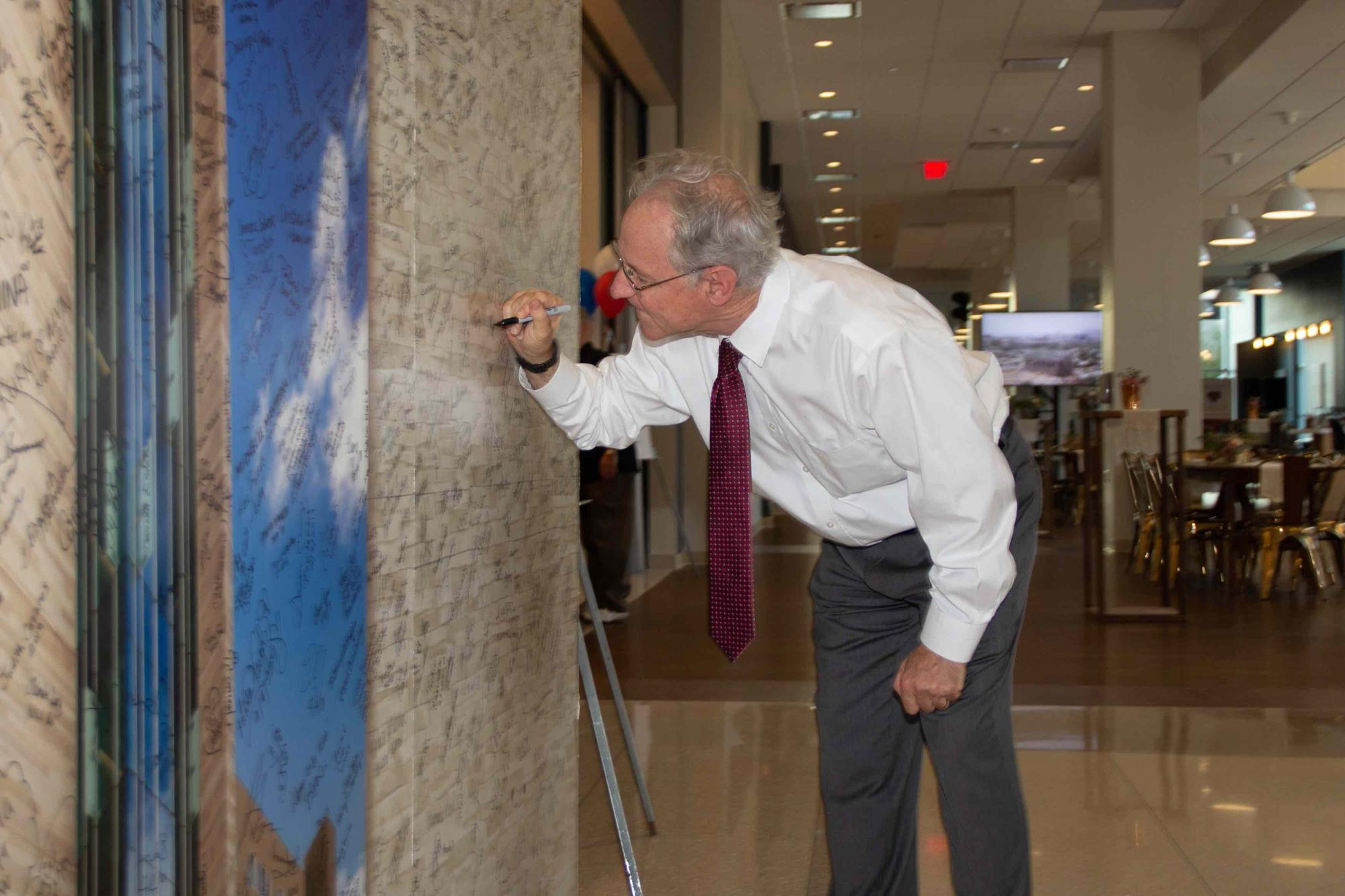 """Tucson Mayor Jonathan Rothschild signs a """"memory wall"""" in Tower 1 during the grand opening reception on April 11."""