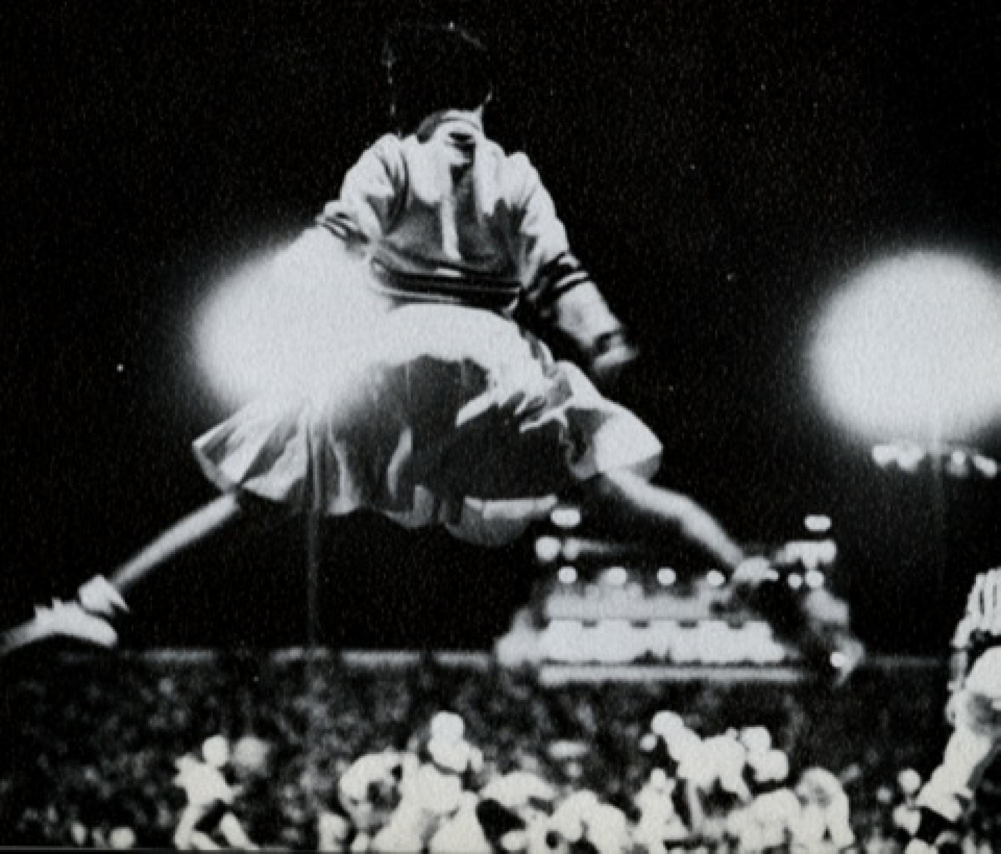 A cheerleader in a mid-air pose during a 1961 football game.