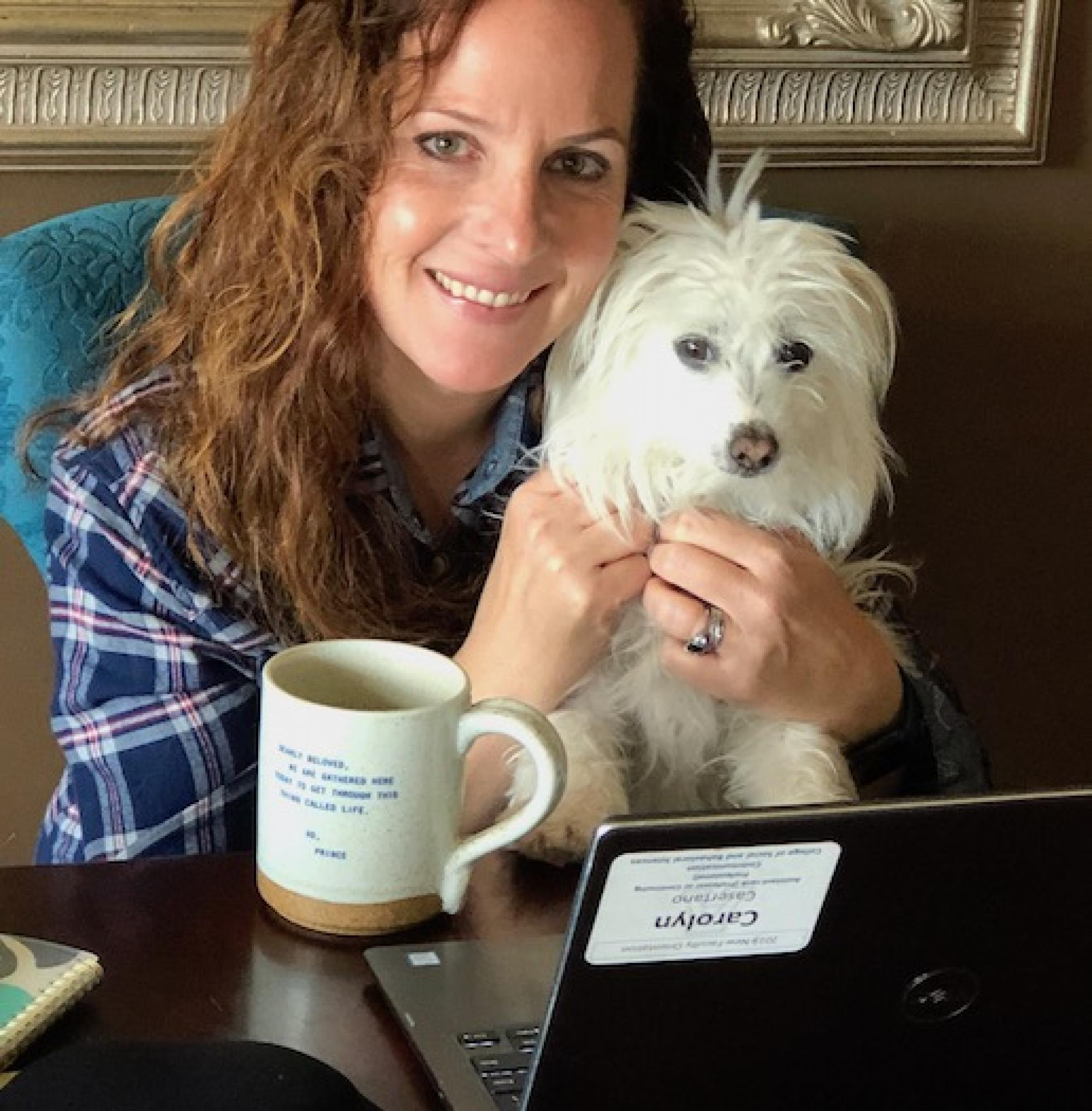 "Carolyn preparing for virtual office hours with help from Cora. Mug with favorite lyric from Prince: 'Dearly beloved, we are gathered here today to get through this thing called life.'"" – Carolyn Casertano, assistant professor of practice in the Departmen"