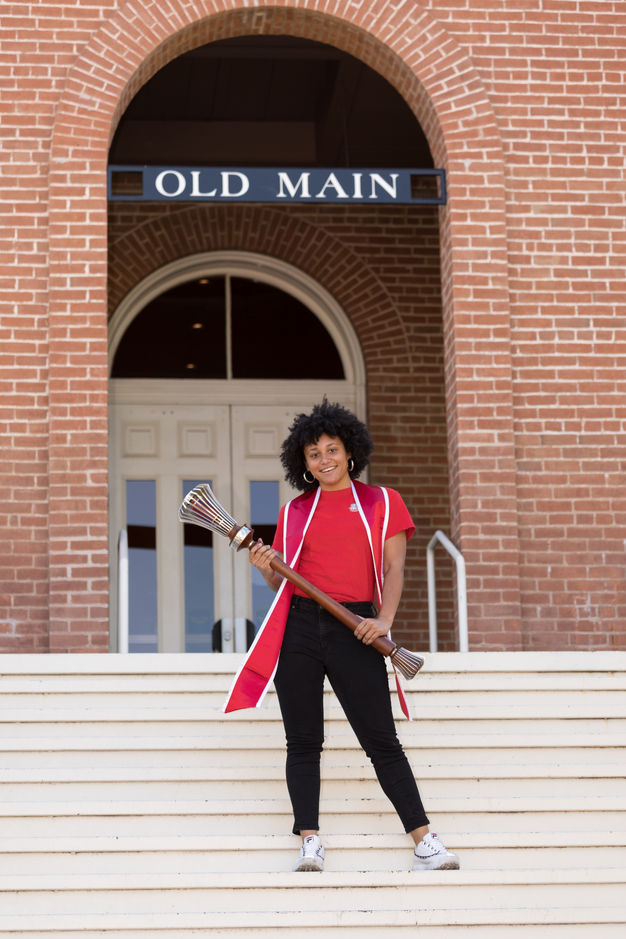 Shelby Young, a senior graduating with degrees in Africana studies and microbiology, poses with the university's ceremonial mace during filming for the virtual 2020 Commencement.