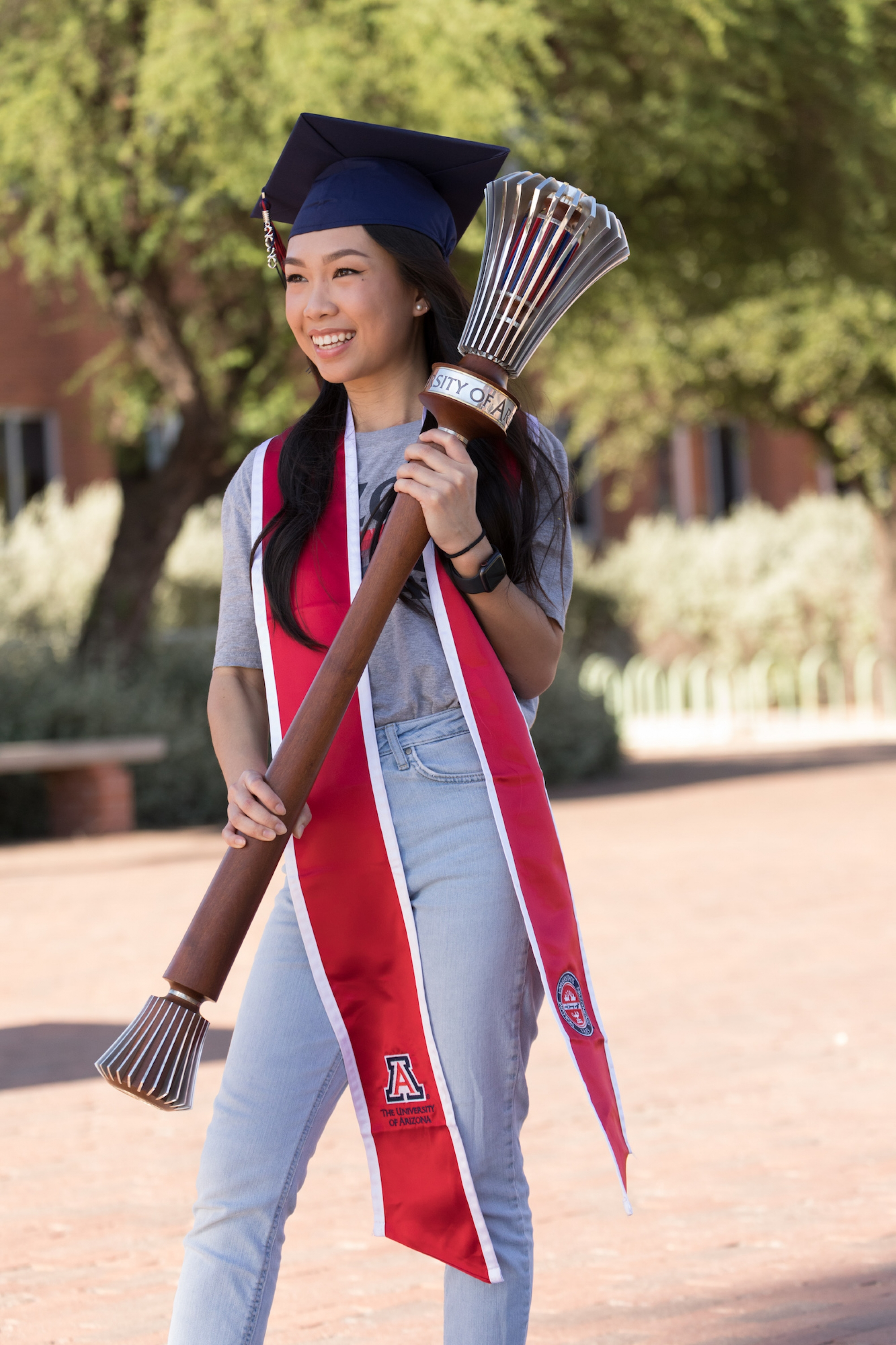 An Luu, a senior graduating with a degree in physiology, poses with the university's ceremonial mace during filming for the virtual 2020 Commencement.