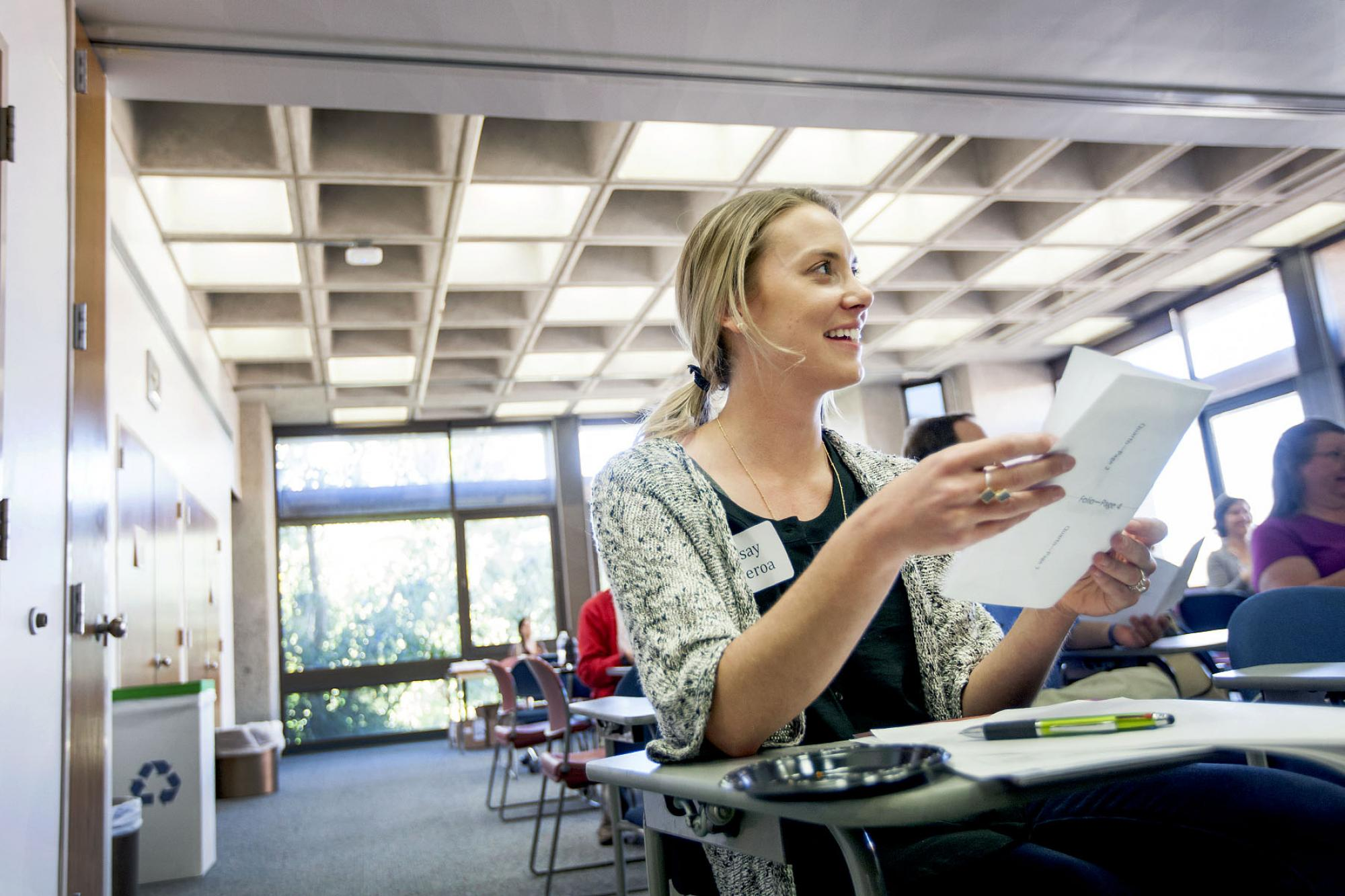 Lindsay Sparks-Figueroa, a 2008 UA alumna and now an English teacher at the Academy of Tucson High School, attempts to fold her own folio out of a handout from the Teacher Training Workshop.