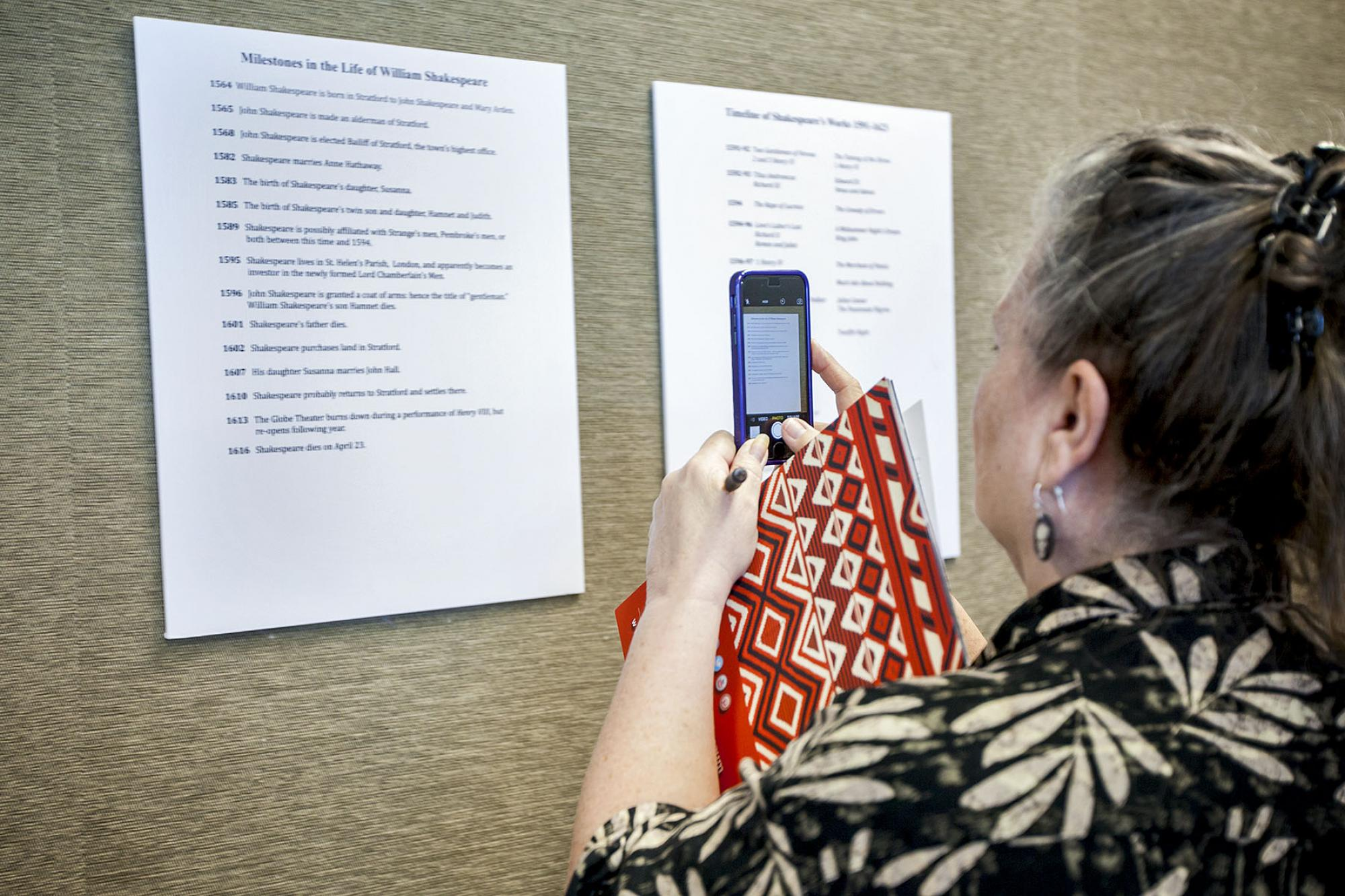 Nicki Navarro, an English teacher from Sahuarita High School, photographs a chronology of milestones in William Shakespeare's life. The timeline is part of the Shakespeare and Elizebathan Culture exhibit at UA Library Special Collections that will be on d
