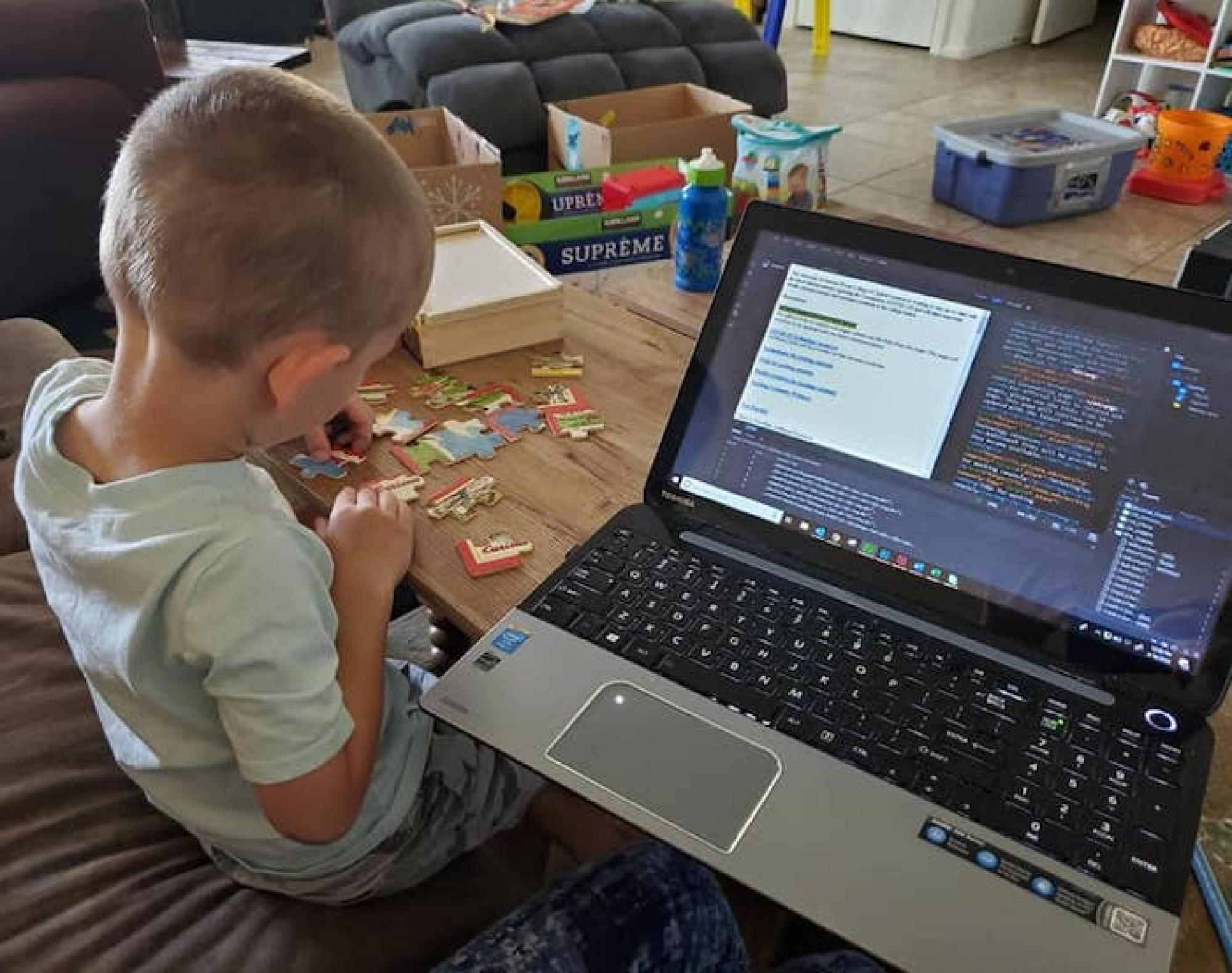 Here's a photo of my son, Joseph , working on puzzles while I'm coding a webpage . Thankfully, we had just purchased a new coffee table a week before this, which has a lift top to turn it into a desk! Overall, we're loving all the family time we're having