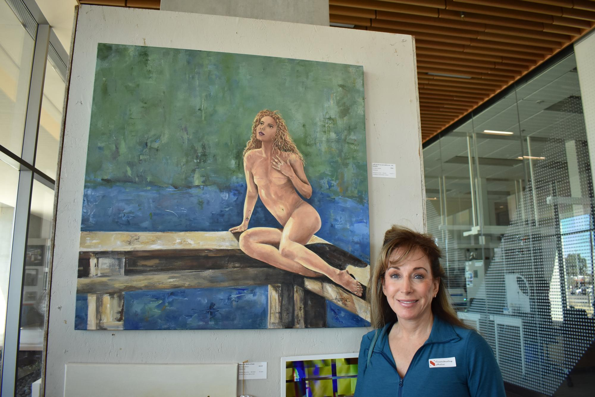 "Harrie Handler, family of Jordan Handler, program coordinator at the University of Arizona BookStores, with her painting, ""I Will Not Be Defined By My Scars. I Am Beautiful."" The painting won a People's Choice Award."