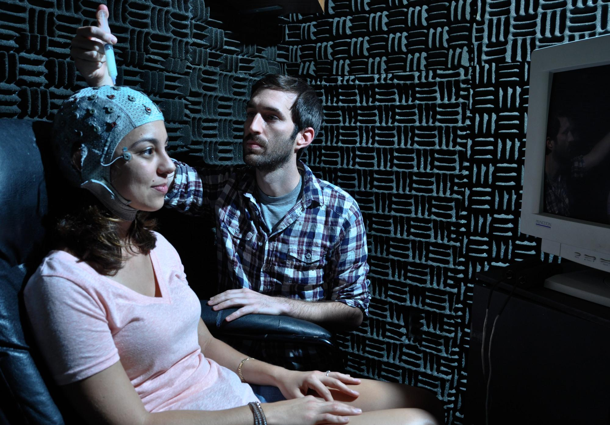Jay Sanguinetti works with Davi Vitela to take EEG scans of her brain activity while she views a series of images for his study.