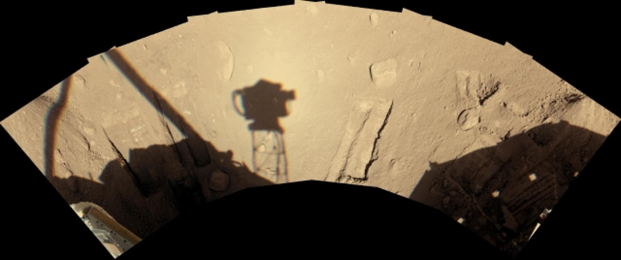 The lander's Surface Stereo Imager camera recorded its view of the workspace on Sol 90, early afternoon local Mars time . The shadow of the camera itself, atop its mast, is just left of the center of the image and roughly a third of a meter  wide.