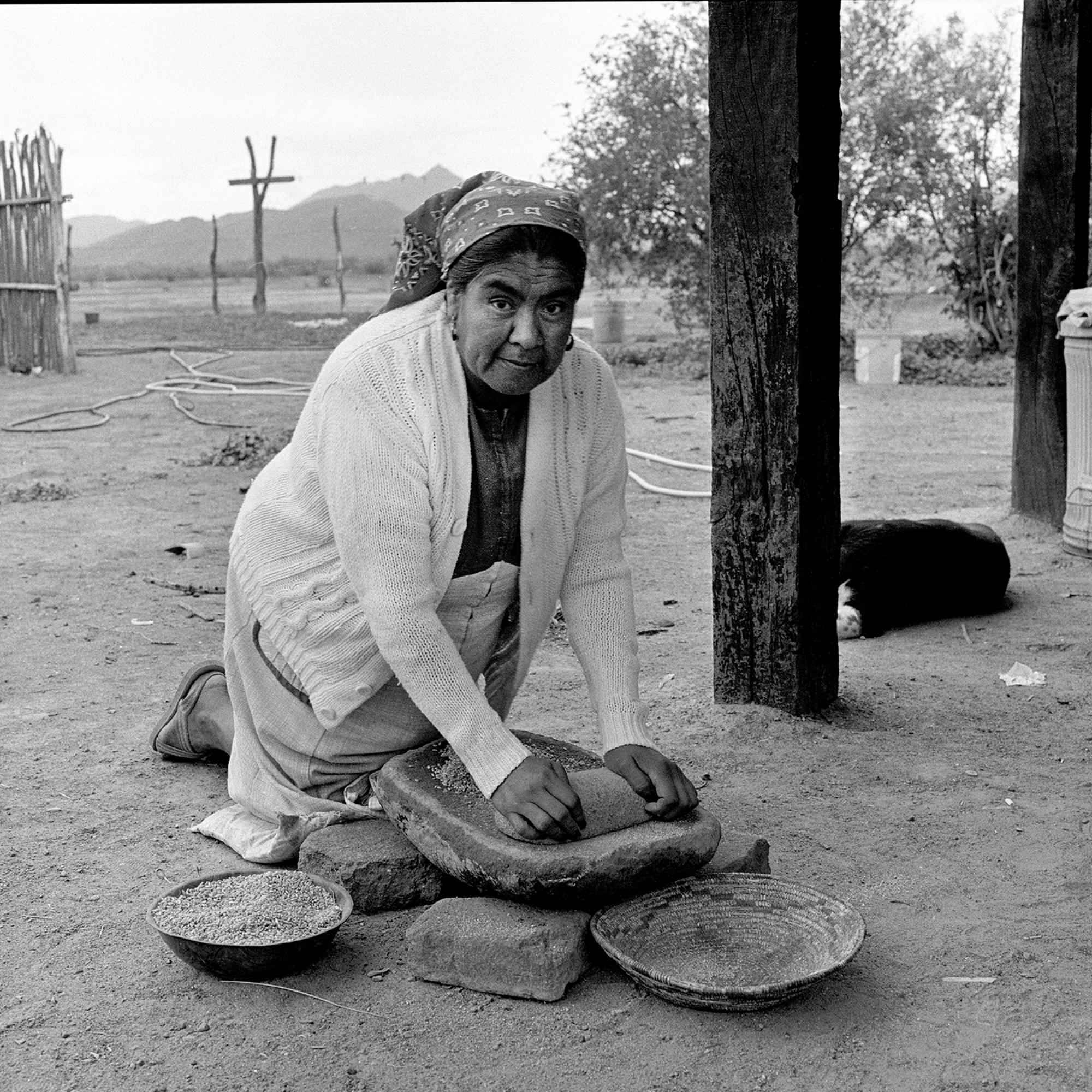 Helga Teiwes took this 1985 photo of Anita Victor grinding wheat on a metate in Meneger's Dam, also known as Ali Chuk, on the Tohono O'odham Nation.