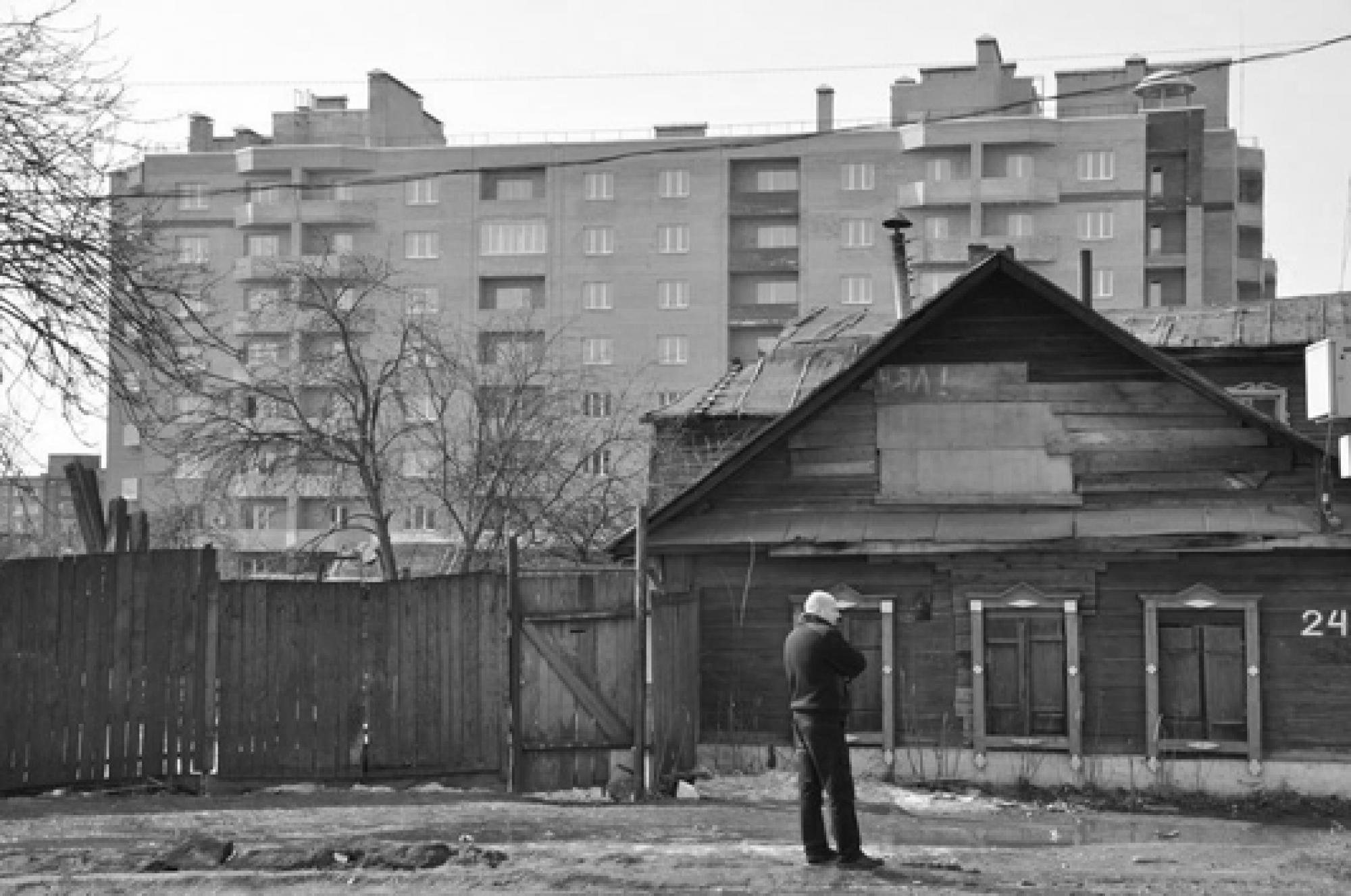 A post-Soviet-era apartment complex looms behind a house that probably predates the 1917 Russian Revolution.