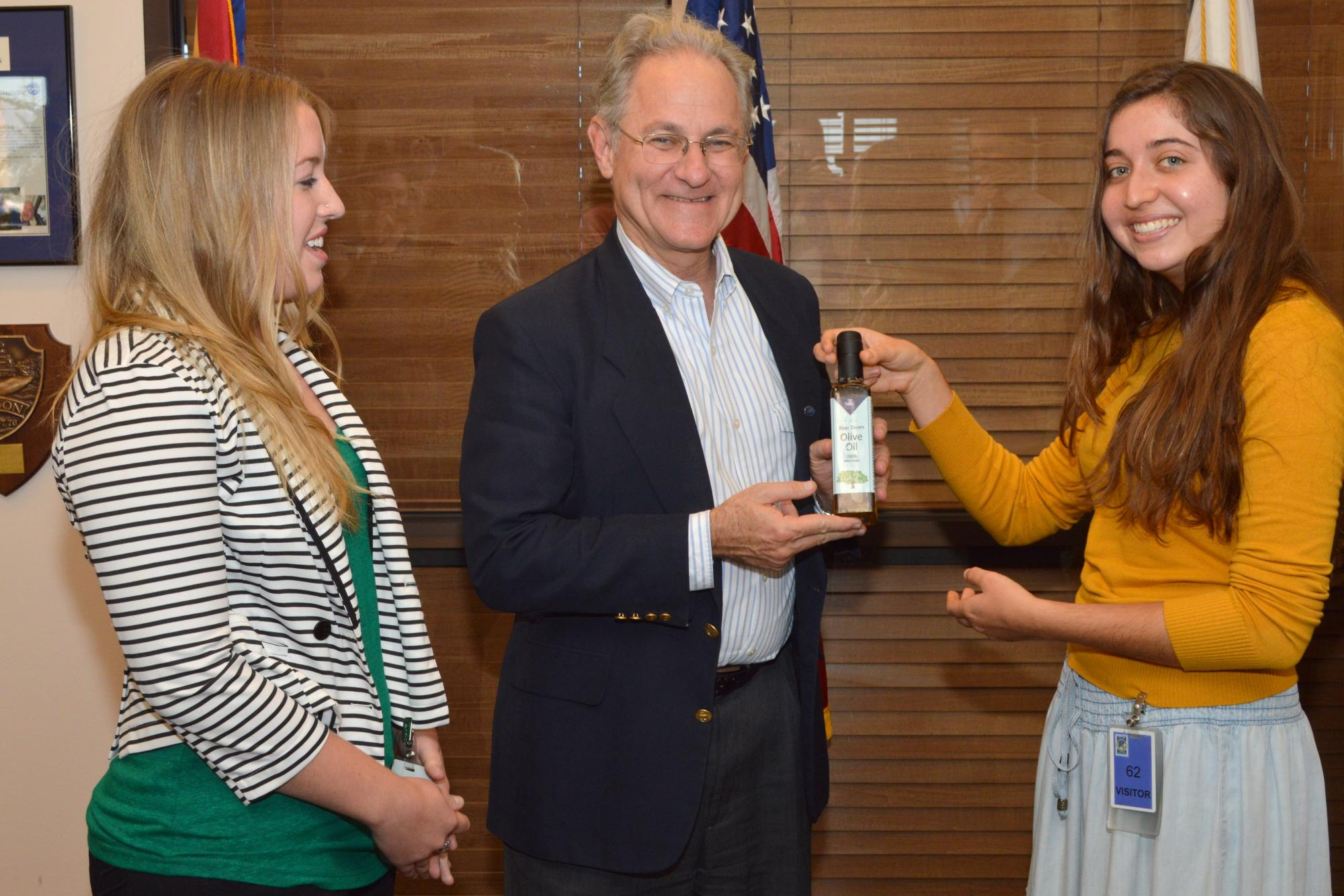 LEAF interns Haley Anderson  and Tori Scaven present Tucson Mayor Jonathan Rothschild on Dec. 5 with a bottle of oil pressed from olives harvested on the UA campus.