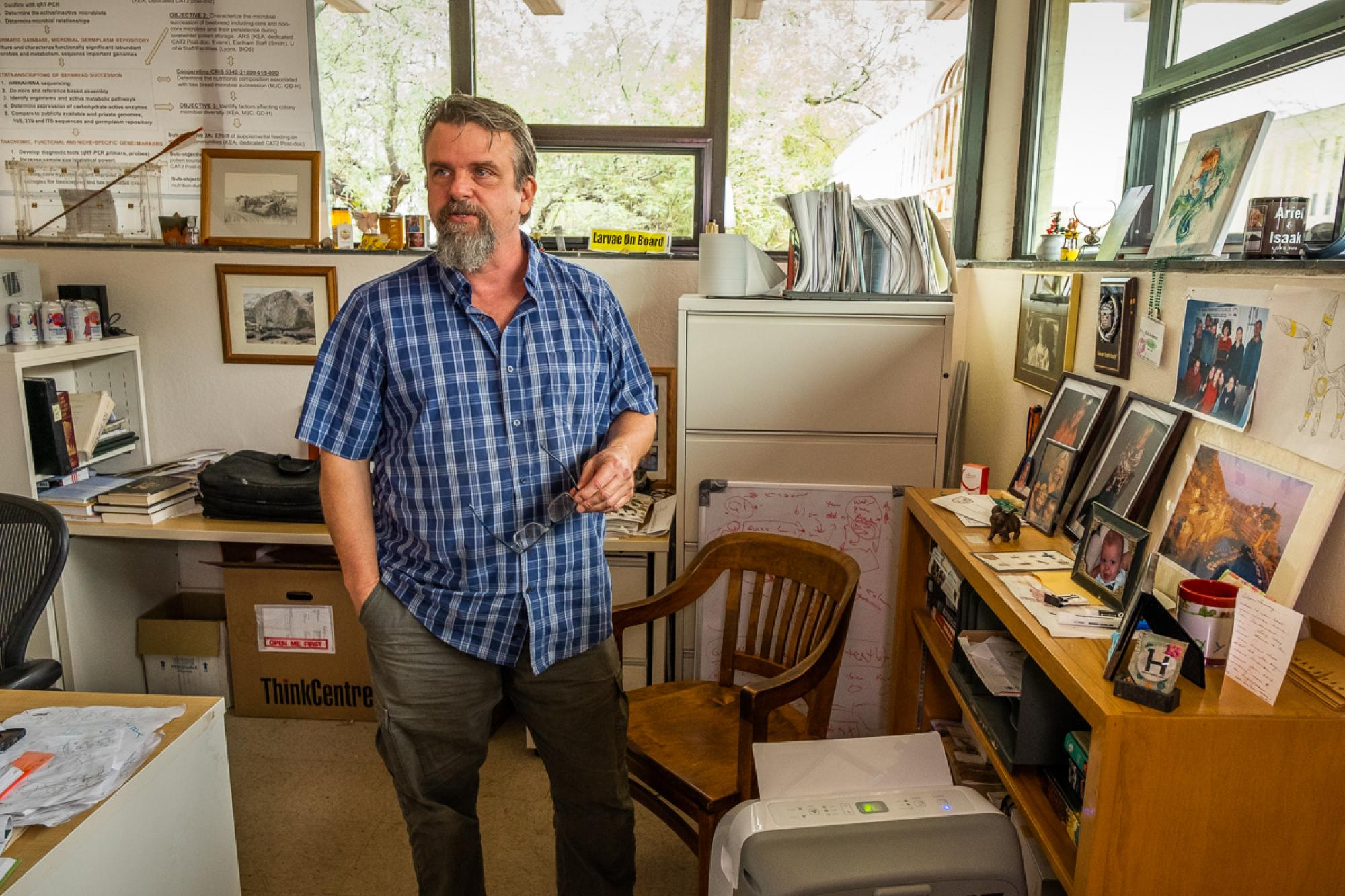 """Kirk Anderson, pictured in his office at the Carl Hayden Bee Research Center in Tucson, grew up on a farm and says he became interested in how complex systems work after spending time fixing combines. """"They're very complex, and some part always breaks,"""" h"""