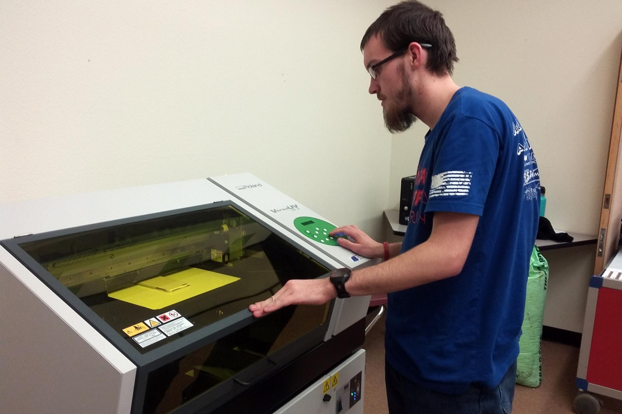 Josh Garrison, a senior at Blue Ridge High School, uses the Roland UV flatbed printer.